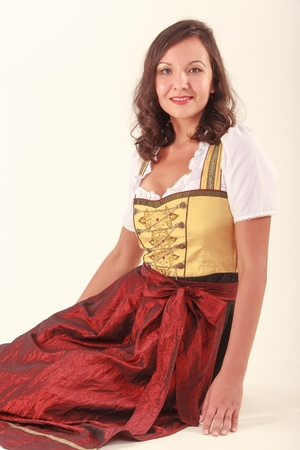 in vouge: Bavarian beauty in costume sitting on the floor