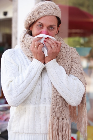 Elderly woman with a cold blows her nose