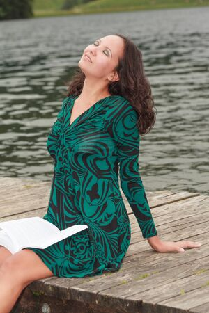 Attractive woman relaxing while reading by the lake Stock Photo - 17624616