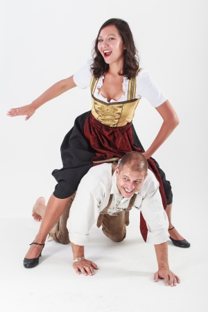Bavarian couple in love with each other jokes in traditional costume Stock Photo