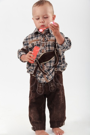 Bavarian boy in leather pants playing with soap bubbles photo
