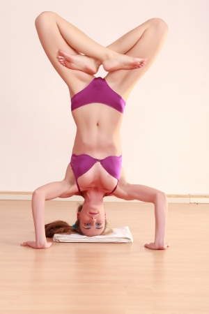 headstand: Young woman in lingerie doing a headstand with legs crossed