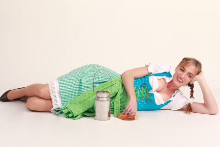 Bavarian girl lying on the floor laughing and playing with milk jug and food