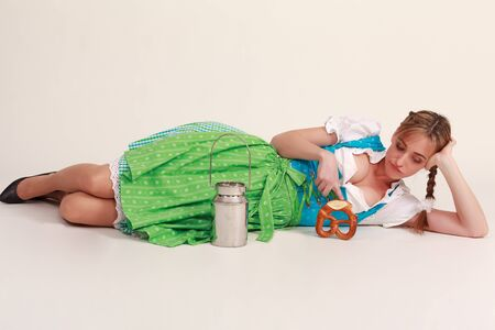 Bavarian girl is bored on the floor and playing with a milk jug and food photo
