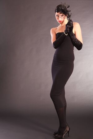 Elegant woman in black catsuit with gun and hair bow Stock Photo - 18208884