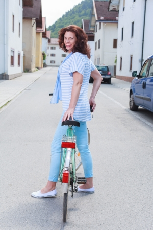 vouge: Older woman in fashionable summer clothes by bike