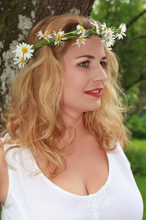 Blonde girl with big breasts in a white linen dress with beautiful lips for kissing leaning against a tree Banco de Imagens