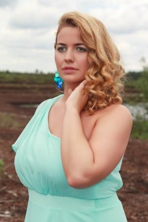 Portrait d une jeune fille blonde avec une grande taille de buste dans une robe de couleur � la menthe
