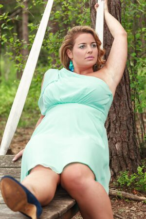 Blond young woman in an oversized aquamarine dress lies on a swing photo