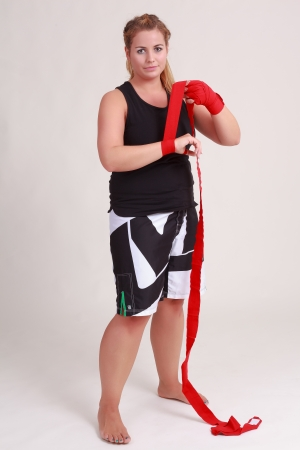 Young blond female boxer is bandaging your hands Stock Photo