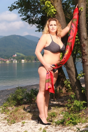 Young chubby woman standing in bikini on the beach with a tree Stock Photo
