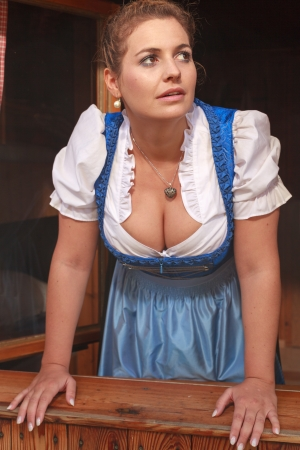 Young peasant woman in a dirndl Look at the weather from a window on the pasture