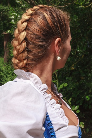 Portrait of a young woman in dirndl with traditional plaits Stock Photo