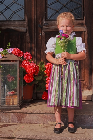 Little girl in a dirndl in front of a farmhouse with a bouquet of flowers photo