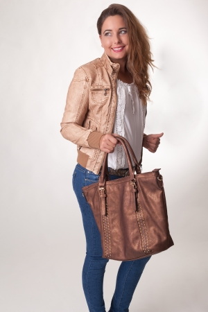 Stylish beautiful young woman with a large brown leather handbag in her hand standing looking back over her shoulder with a friendly smile, studio portrait