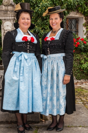 berchtesgaden: Two charming ladies in traditional dirndls with festive red flowers tucked into the bodices of the dresses standing together outdoors Stock Photo