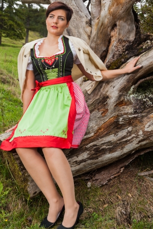 Pretty young brunette woman in a traditional dirndl relaxing on an old tree trunk with a jacket thrown loosely over her shoulders