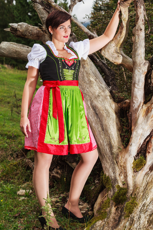 Fashion Shot of a young Bavarian woman in dirndl with oversize, standing on an old tree stump on a mountain meadow photo