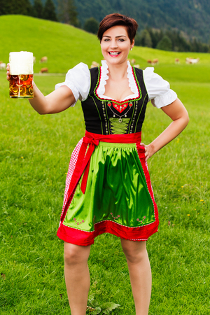 liter: Happy young woman in a dirndl with a large glass tankard of frothy beer raised in her hand in a toast as she stands in a lush green mountain pasture Stock Photo