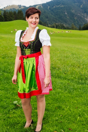Beautiful stylish young Bavarian woman in a colourful embroidered red and green dirndl standing smiling happily in a lush green mountain meadow