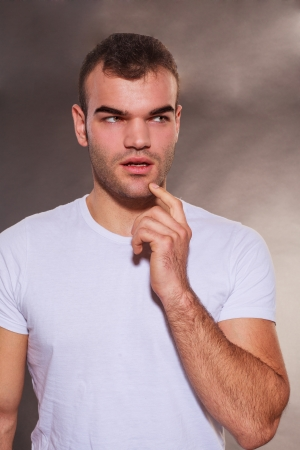 Thoughtful attractive unshaven young man planning and scheming standing with his finger to his chin, parted lips and a pensive expression photo