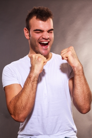 exultant: Jubilant exultant unshaven young man cheering and making fists with his hands as he celebrates a success or victory