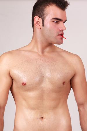 nackte brust: Close up Torso Blick auf die nackte Brust einer Passung junger Mann isoliert auf grau, mit Lutscher in den Mund Lizenzfreie Bilder