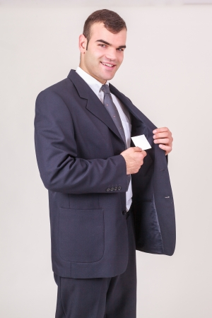 breast pocket: Stylish handsome young businessman smiling at the camera takes a business card from his breast pocket of his jacket, on white, three-quarters