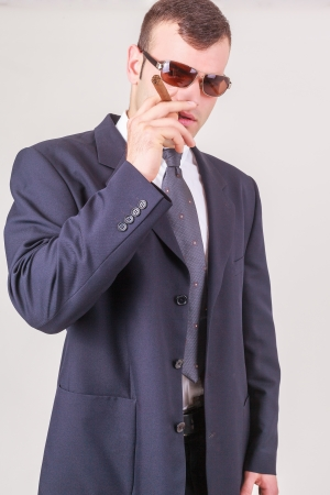 suave: Suave successful businessman or CEO standing in a pair of sunglasses in his suit puffing on a big cigar Stock Photo