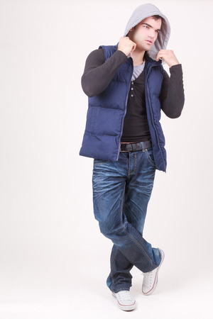 Relaxed charismatic young man in a hooded anorak top and jeans standing cross legged laughing at the camera, full length on white