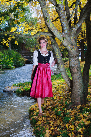 sultry: Beautiful woman in a dirndl posing in an autumn park with one foot raised to reveal her bare leg as she leans towards the camera with a sultry sexy look