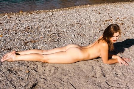 desnudo de mujer: Hermosa mujer desnuda con una figura atractiva que miente en una playa en su est�mago el tomar el sol la arena bajo el sol caliente del verano, vista de �ngulo alto