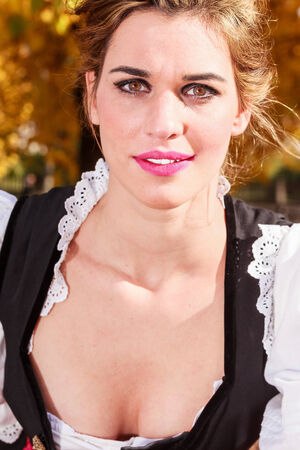 Close up face portrait of a beautiful young German woman with brown eyes wearing makeup in a traditional dirndl looking up at the camera