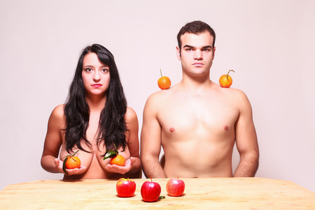 deadpan: Conceptual image of a young nude man and woman posing with fresh tropical fruit in their hands and balanced on their shoulders looking at the camera with serious expressions as they sit at a table