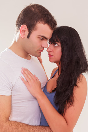 Loving young couple looking into each others eyes with tender anticipation as they stand close together with their foreheads touching, Stock Photo