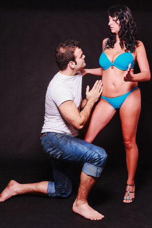 Young couple acting out sexual fantasies of dominance and subservience with the barefoot man kneeling at the womans feet as she stands in her lingerie gripping him by the shirt photo