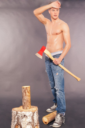 spattered: Muscular handsome young man in paint spattered jeans, sneakers and a bare chest standing chopping logs with an axe on a grey studio background