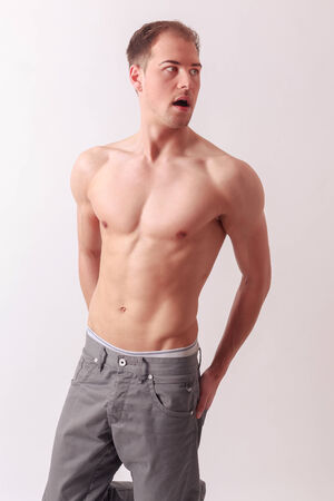 Handsome athletic man with a strong physique posing shirtless and barefoot balanced on one leg on a studio background photo
