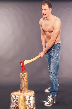 spattered: Apuesto joven muscular en la pintura salpic� los pantalones vaqueros, zapatillas de deporte y un pecho desnudo de pie registros de cortar con un hacha en un estudio de fondo gris