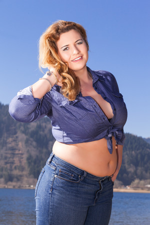 Attractive curvaceous woman with a beautiful smile and her hair blowing in the breeze posing in the sunshine at the seaside in a knotted short top with bare midriff Standard-Bild