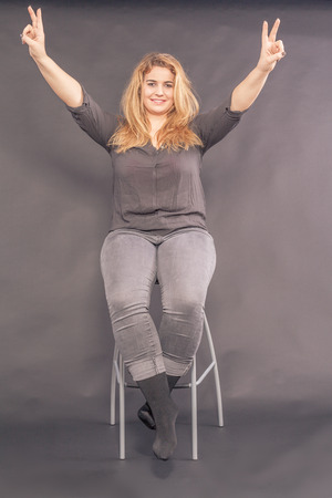 Happy attractive woman sitting on a stool making a V-sign with both her hands for peace or victory as she smiles at the camera
