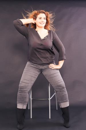 Jonge mooie vrouw met overgewicht zittend op een barkruk in denim shirt en jeans, met wapperende haren, studio-opname Stockfoto