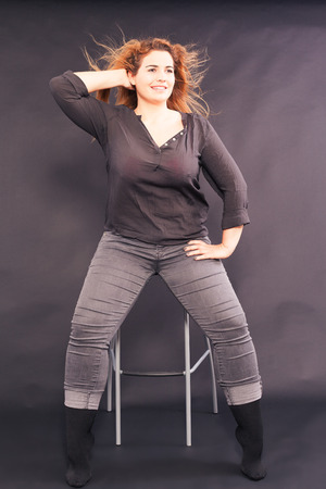 Young pretty woman with overweight sitting on a bar stool in denim shirt and jeans, with fluttering hair, studio shot Stock Photo