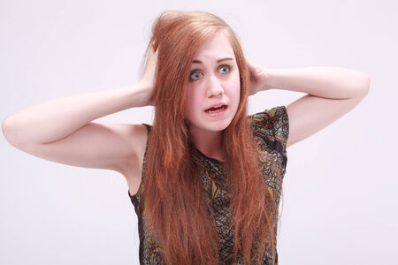 nervousness: Female model with hands on both sides of her head looking frustrated