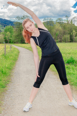 Smiling woman exercising doing side stretches outdoors photo