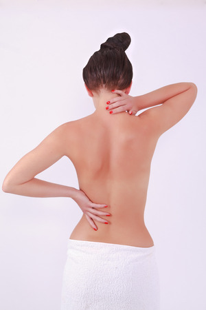 half body: woman with aching back and neck on white background Stock Photo