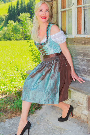 the latest models: Laughing blonde woman in Bavarian Dirndl is sitting on a wooden bench in front of an old farm Stock Photo