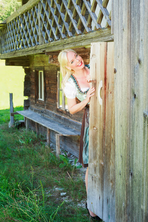 toilet door: Young blond woman in dirndl looks out of the toilet door in an old historic farm