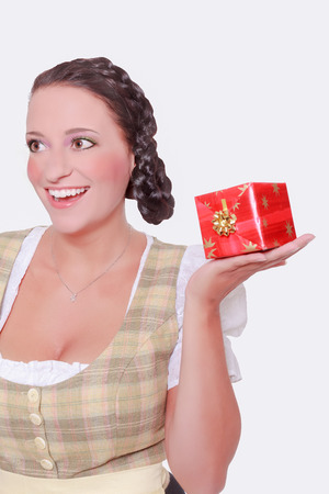 trenzas en el cabello: Mujer joven en Dirndl y el pelo trenzado tiene un regalo en la palma de su mano. Foto de estudio - aislados en blanco