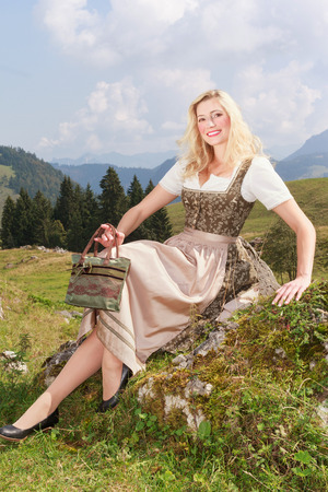 Young attractive blond woman in dirndl sitting sunning on a rock in the mountains